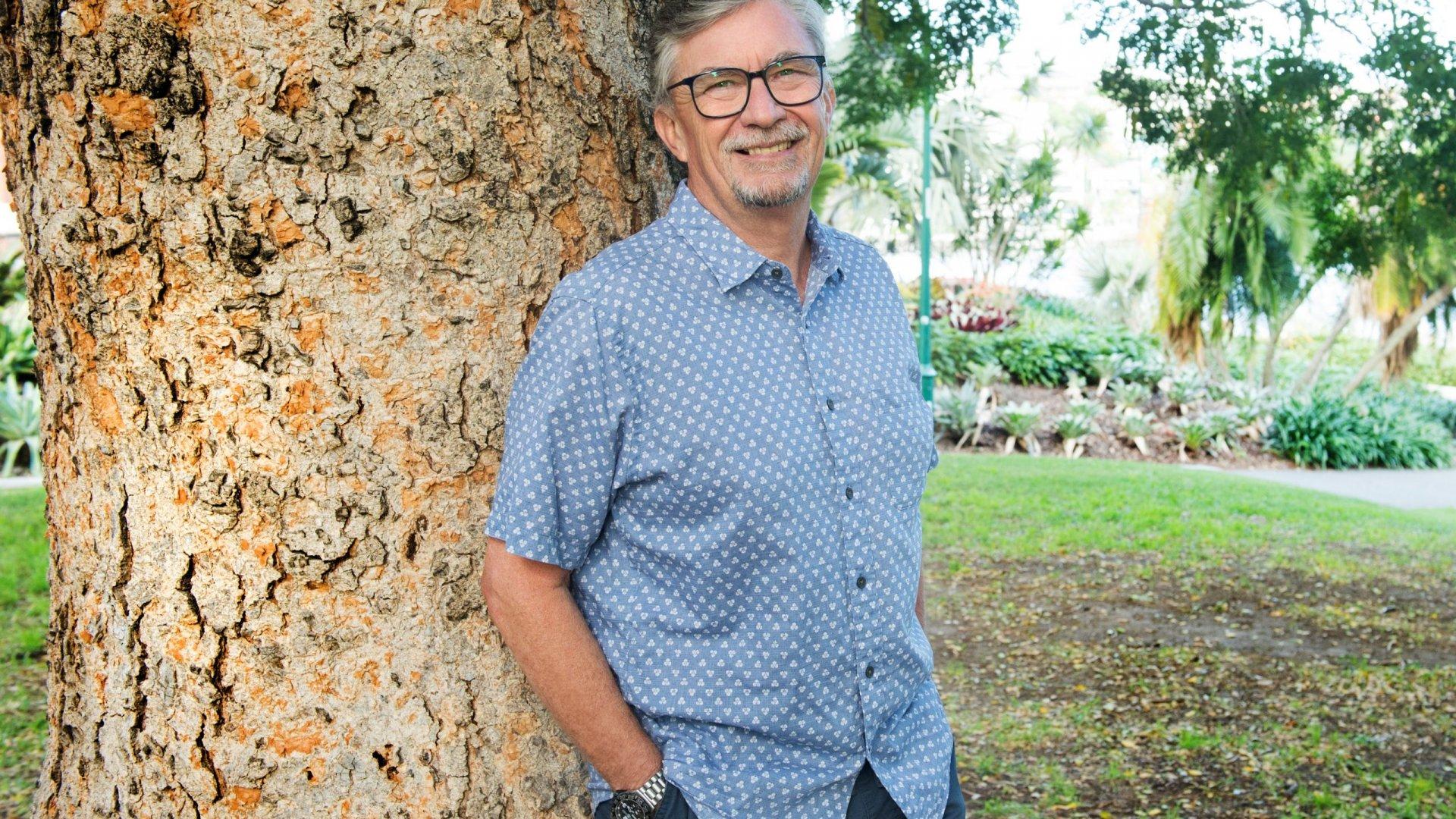 man standing under tree